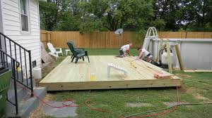 rectangular wooden deck with white round pool above ground plus