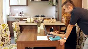 couple of young people working on laptop in dining room at home