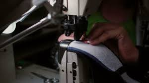 woman making a smooth seam on sewing machine worker sew leather
