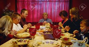family praying around thanksgiving table stock photo picture and