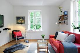 small living room idea with shocking red sofa and white walls
