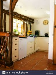 quarry tiled floor in cottage kitchen with exposed wall beams and