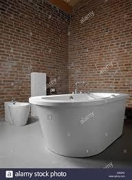 modern bathroom with brick walls concrete floor and the bathtub