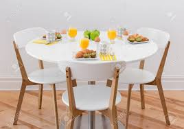 White Circle Table by White Round Table With Healthy Breakfast For Three Stock Photo