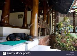dog resting on front porch of old indian wooden style kerala house