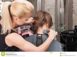 female hairdresser cutting hair of man client using trimmer stock