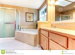 refreshing bathroom with light wood cabinets glass shower and b