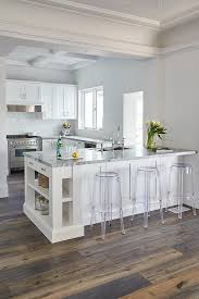 peninsula island kitchen backless acrylic stools sit in front of a white kitchen peninsula