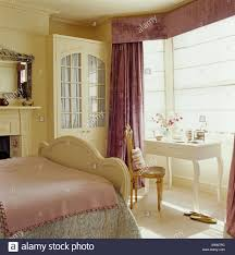 purple heavy silk curtains and cream blind on bay window in