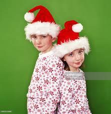siblings wearing matching pajamas and santa hats portrait stock