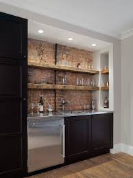 kitchens with brick walls with backsplash and sink also various glass in cabinets and brick