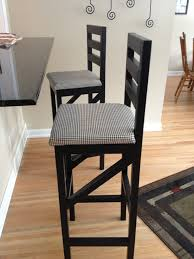 black wooden bar stool with back and patterned seat cover on
