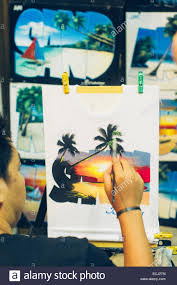 artist is painting on a shirt as design photo is taken at boracay