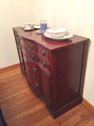 buffet with three drawers and round dining table with side chair