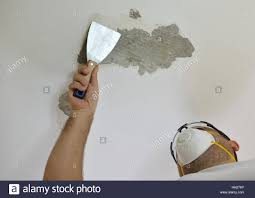 man scraping a ceiling with a plaster spatula preparing it for