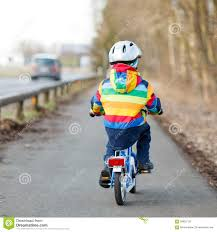 bike raincoat kid boy in safety helmet and colorful raincoat riding bike outd