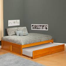 brown polished wooden trundle bed frame and bed with pillow