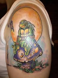 turtle sit on mushroom tattoo on left shoulder
