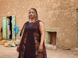 picture of heavy set women in a two piece bathing suit forcefeeding in mauritania west africa fat c