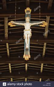 a statue of jesus on the cross hanging from the ceiling of st