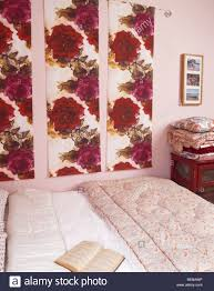 small pink bedroom with red rose patterned fabric panels on wall