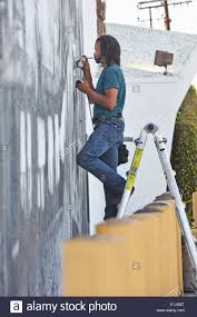 artist painting mural on the wall of an italian restaurant notting male african american airbrush artist on step ladders painting mural stock photo