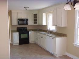 white stained wooden kitchen cabinet with marble eased edge