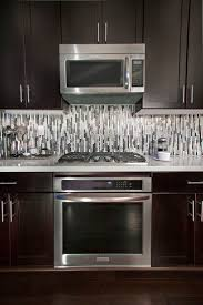top 25 best modern kitchen backsplash ideas on pinterest to accentuate the modern lines within we laid the quartz metal and glass backsplash tile vertically to our homeowners delight this kitchen has become an