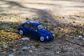 volkswagen yellow car vehicle retro red and white beetle car toy on grass field in bokeh photography