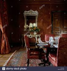red upholstered chairs in dining room with mirror and oriental rug