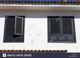 black painted sun shutter blinds on windows of white washed house