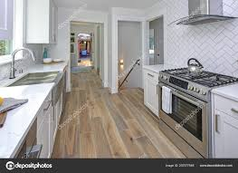 white kitchen cabinets with marble counters remodeled kitchen with white cabinets marble countertops herringbone backsplash and stainless steel appliances 207577548