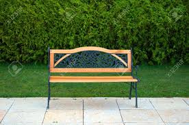 nice little cast metal and wooden bench in front of the green
