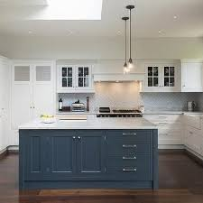 white kitchen cabinets with blue island gray herringbone kitchen backsplash tiles transitional