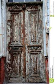 aged weathered wooden entrance doors with peeling paint stock