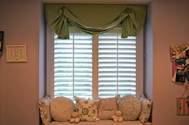 green roll up valance with white wooden curtains and window sea