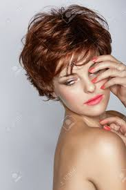 beautiful young woman with short brown haircut wears pink lipstick