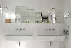 floating white trough bathroom sink with two faucets on beadboard