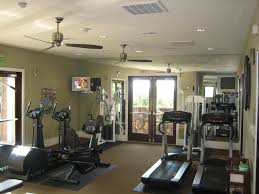 traditional home gym with ceiling fan u0026 hardwood floors in