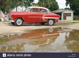 old classic american car with water reflection and house in stock
