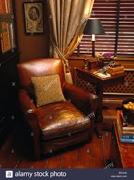 brown leather armchair next to side table with lighted lamp in