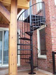 black wrought iron spiral staircase connected by brick wall and