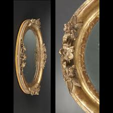 oval mirror within a carved and re gilt wood frame early 18th