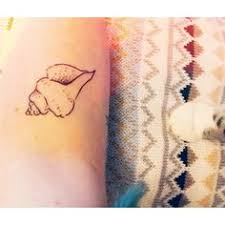 shell tattoo in white to look like a birthmark of a mermaid as