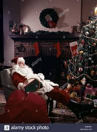 santa claus asleep in chair in front of christmas tree and
