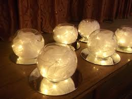lighted candle with a large fishbowl with lights and