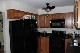medium light shaker style cabinetry with black appliances and
