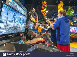 two young men playing video shooting games with guns in an arcade