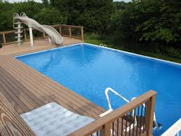 wooden pool deck with seating area for large above ground backyard