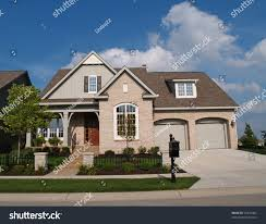 small beige brick home with a two car garage in the front stock